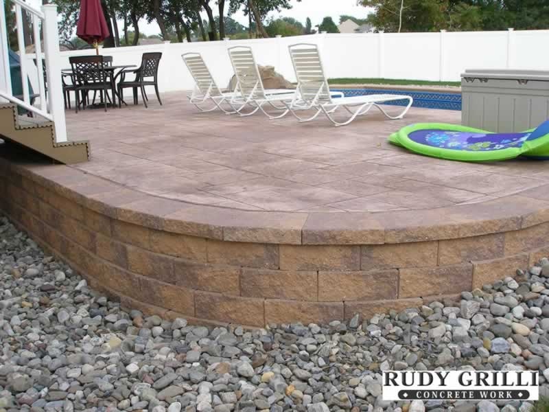 Raised Stamped Concrete Patio With Paver Columns And Steps